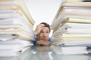 A stressed out business man with a lot of paperwork not using document management properly