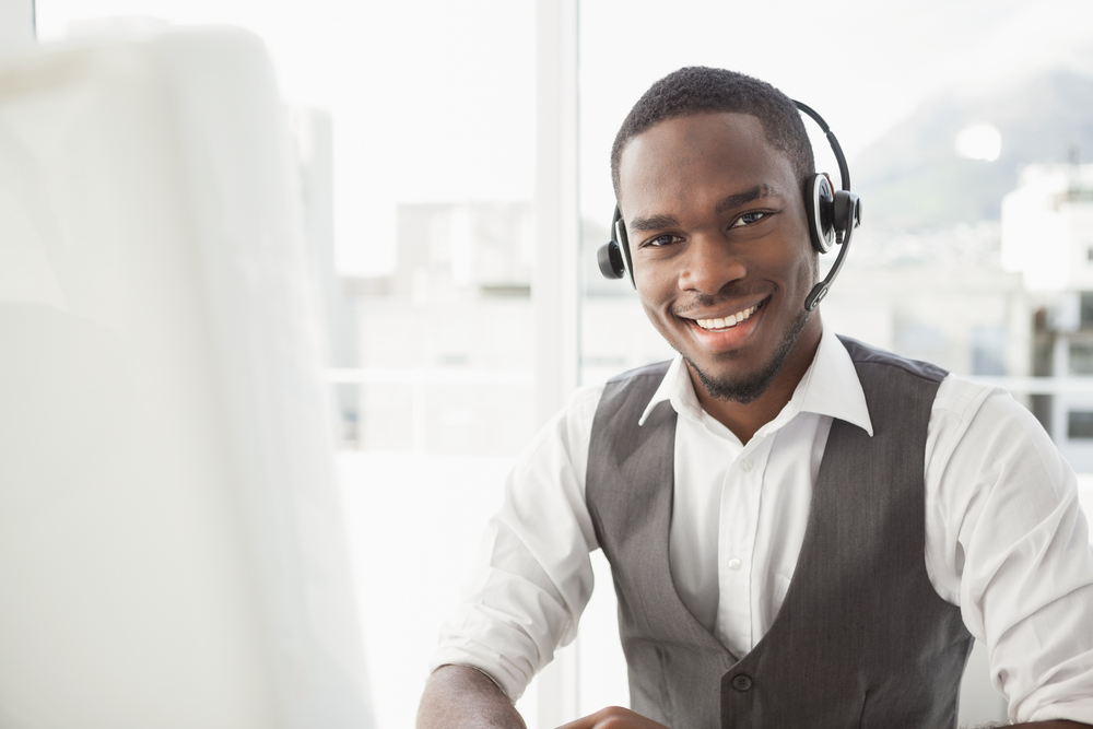 Happy businessman with headset interacting in his office-1